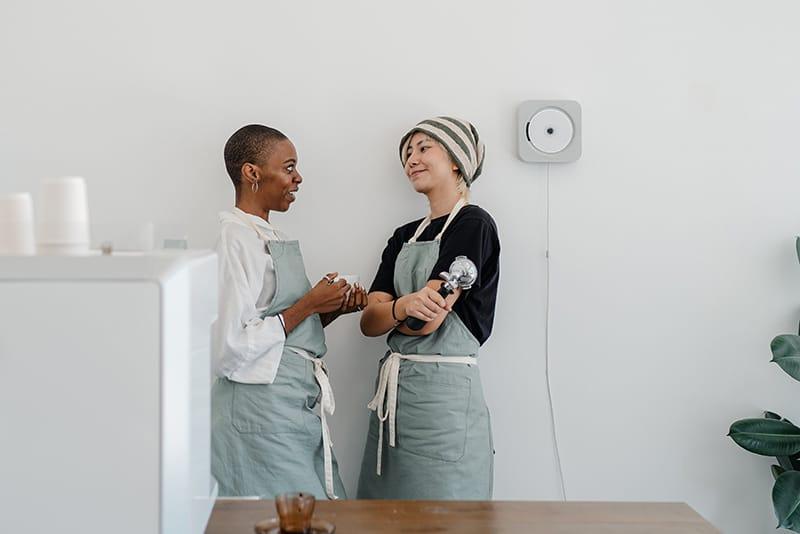 zwei lächelnde Kolleginnen sprechen bei der Arbeit