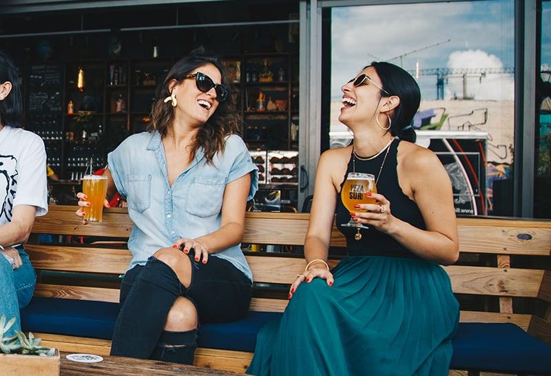 zwei lachende Frauen, die Getränke halten, während sie auf der Holzbank sitzen