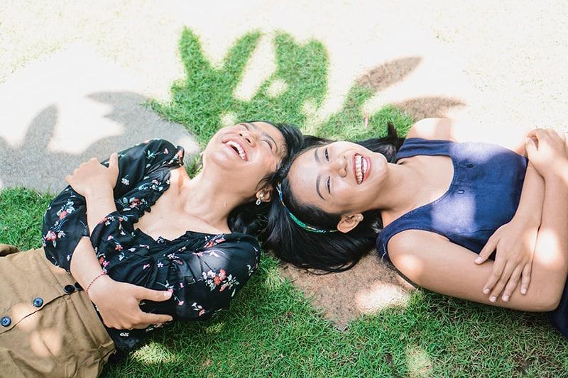zwei lachende Frauen, die auf dem grünen Gras liegen