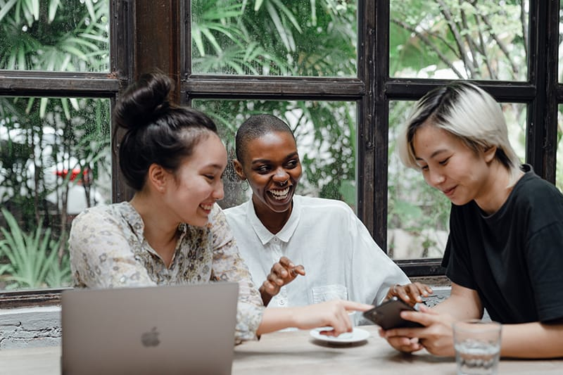 zwei lachende Frauen, die ihre Freundin ansehen, während sie ein Smartphone benutzt, das am Tisch sitzt