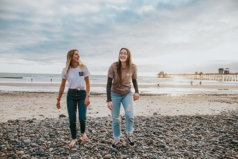 zwei lachende Freundinnen, die nahe dem Strand gehen