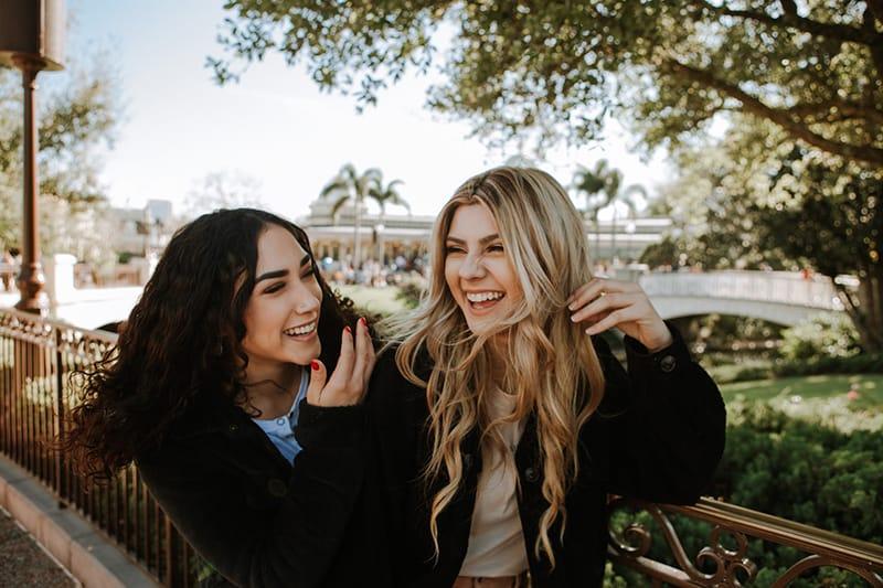 zwei lachende Freundinnen, die nahe dem Zaun auf dem Bürgersteig stehen