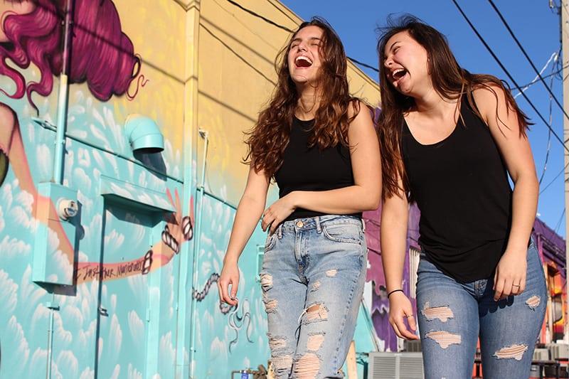 zwei lachende Mädchen, die zusammen nahe der Graffitiwand gehen