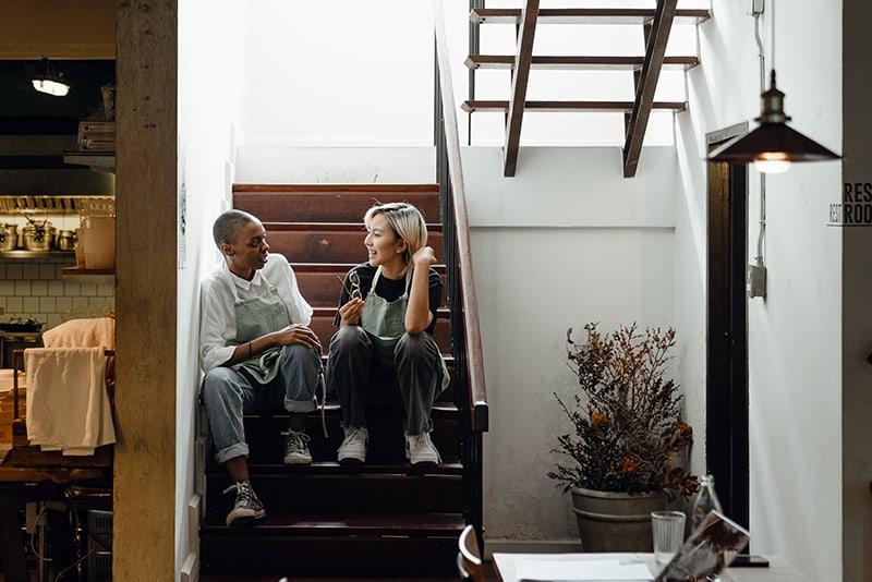 zwei weibliche Mitarbeiter plaudern während einer Pause auf Treppen