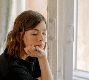 eine nachdenkliche Frau, die sich auf Holzfenster stützt
