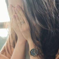 eine traurige Blondine hält ihr Gesicht mit den Händen