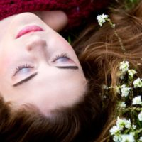 Die Frau liegt mit geschlossenen Augen im Gras
