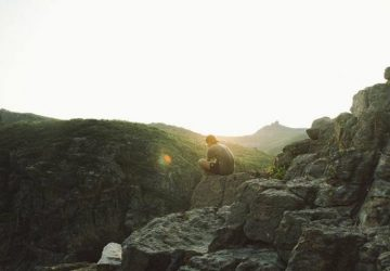 Ein einsamer Mann sitzt auf einem Hügel