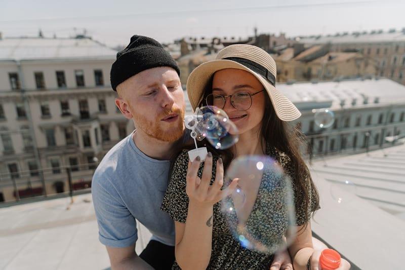 Ein Mann und eine Frau machen zusammen Seifenblasen
