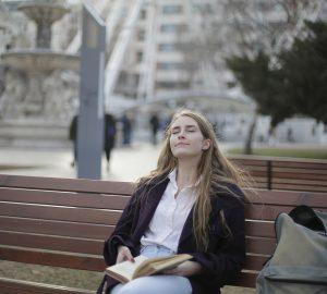 Eine Frau mit geschlossenen Augen sitzt mit einem Buch in den Händen auf der Bank