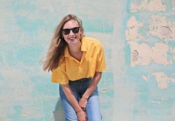 lächelnde Frau, die sich an die blaue Wand lehnt