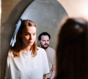 ein unglückliches Paar, das vor dem Spiegel steht
