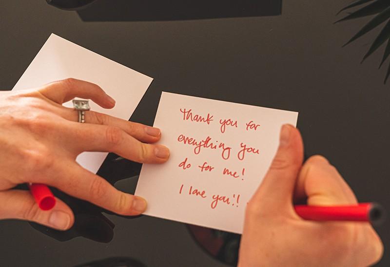 eine Person, die eine Notiz auf den Tisch schreibt