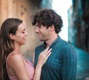 Ein lächelnder Mann und eine lächelnde Frau stehen sich gegenüber, während sie auf der Straße nahe beieinander stehen