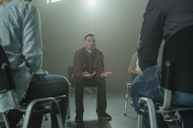 Ein Mann spricht mit der Familie, während er auf dem Stuhl bei der Therapie sitzt