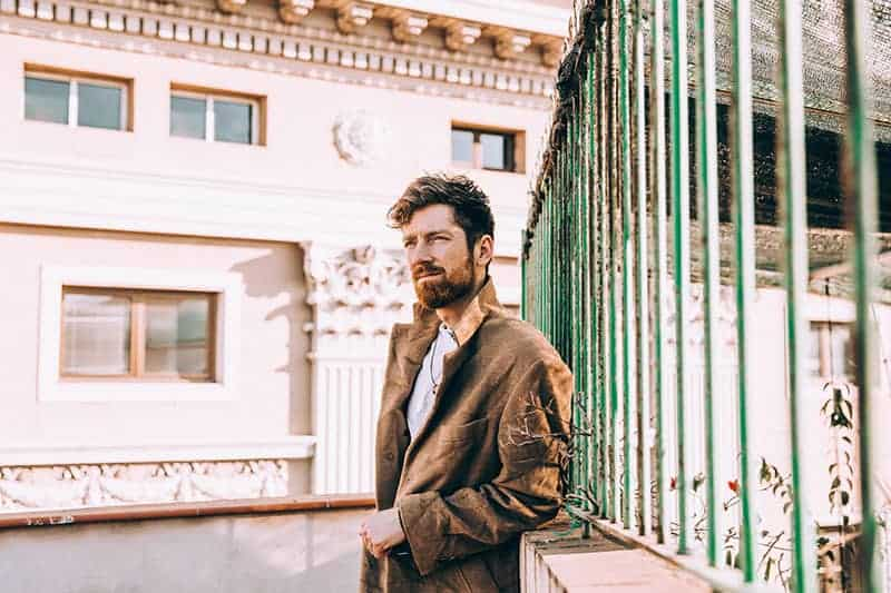 Ein Mann mit Bart steht in einem braunen Mantel am Zaun