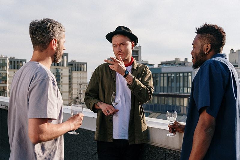 Ein Mann mit Hut, der mit Freunden spricht, während er auf dem Dach steht