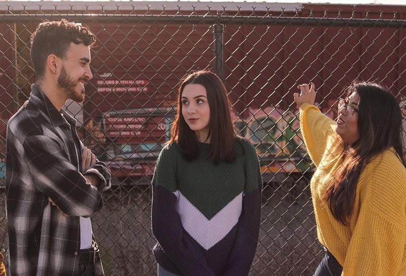 Ein Mann mit verschränkten Armen spricht mit zwei Freundinnen, während er in der Nähe des Zauns steht