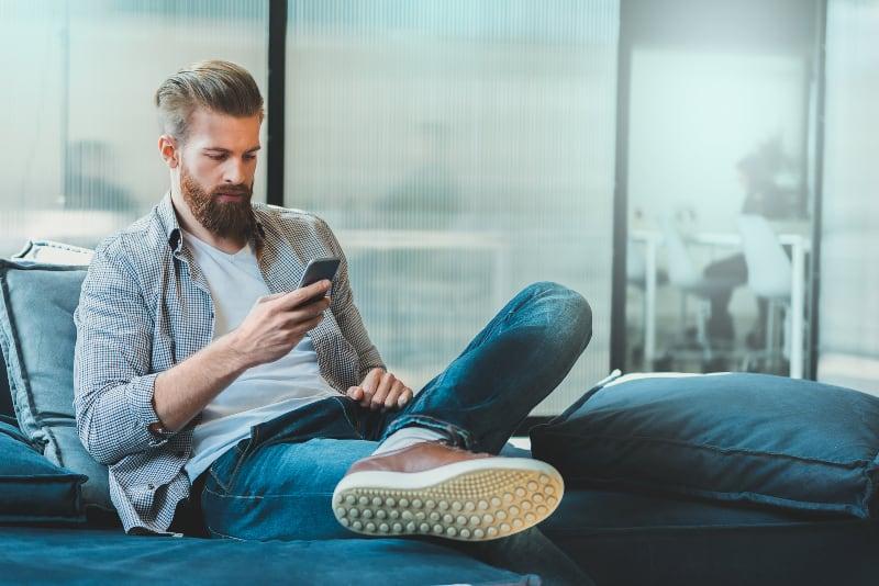Ein Mann sitzt auf der Couch und tippt eine Nachricht
