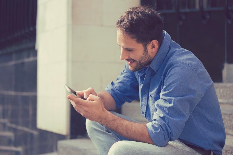 Ein Mann sitzt auf der Treppe und hat einen Knopf auf seinem Handy