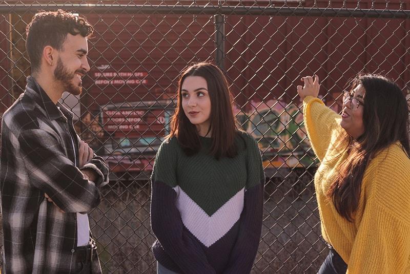 Ein Mann spricht mit zwei Freundinnen, während er in der Nähe des Zauns steht