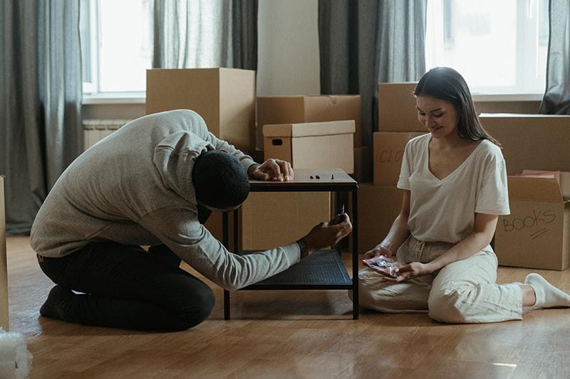 Ein Mann stellt einen Tisch zusammen, während eine Frau nebeneinander auf dem Boden sitzt