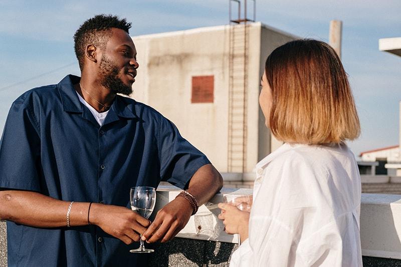 Ein Mann und eine Frau flirten, während sie zusammen auf dem Dach etwas trinken