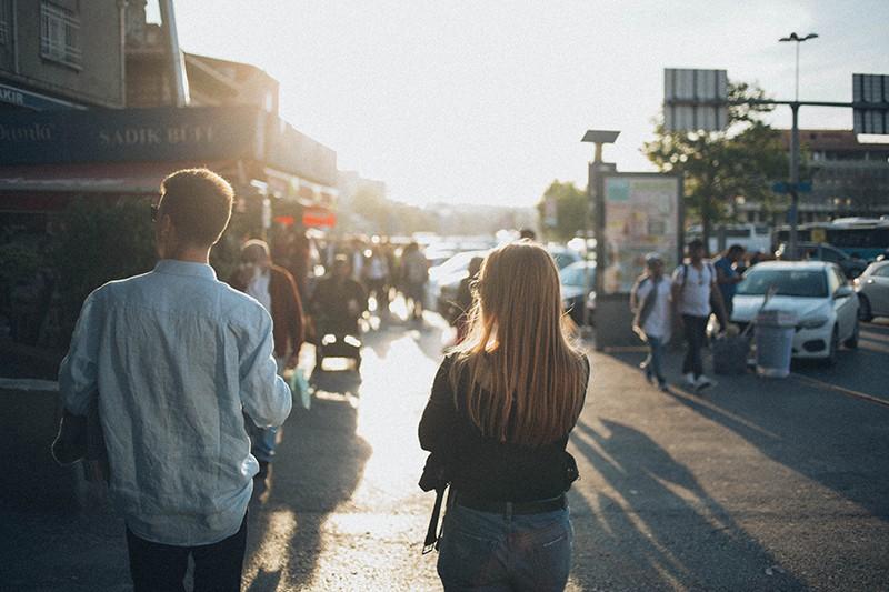 ein Mann und eine Frau, die während des Sonnenuntergangs auf der Straße gehen