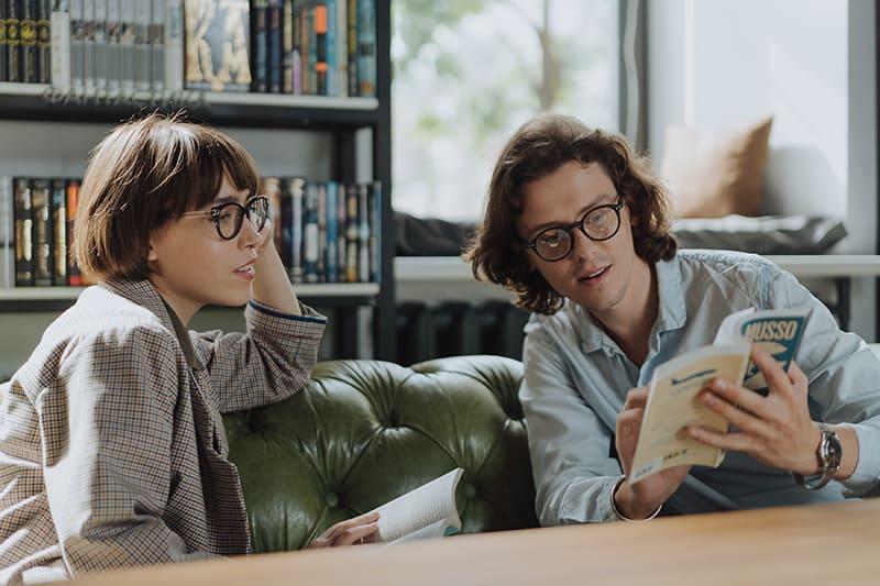 Ein Mann und eine Frau lesen zusammen ein Buch, während sie zusammen in der Bibliothek rumhängen