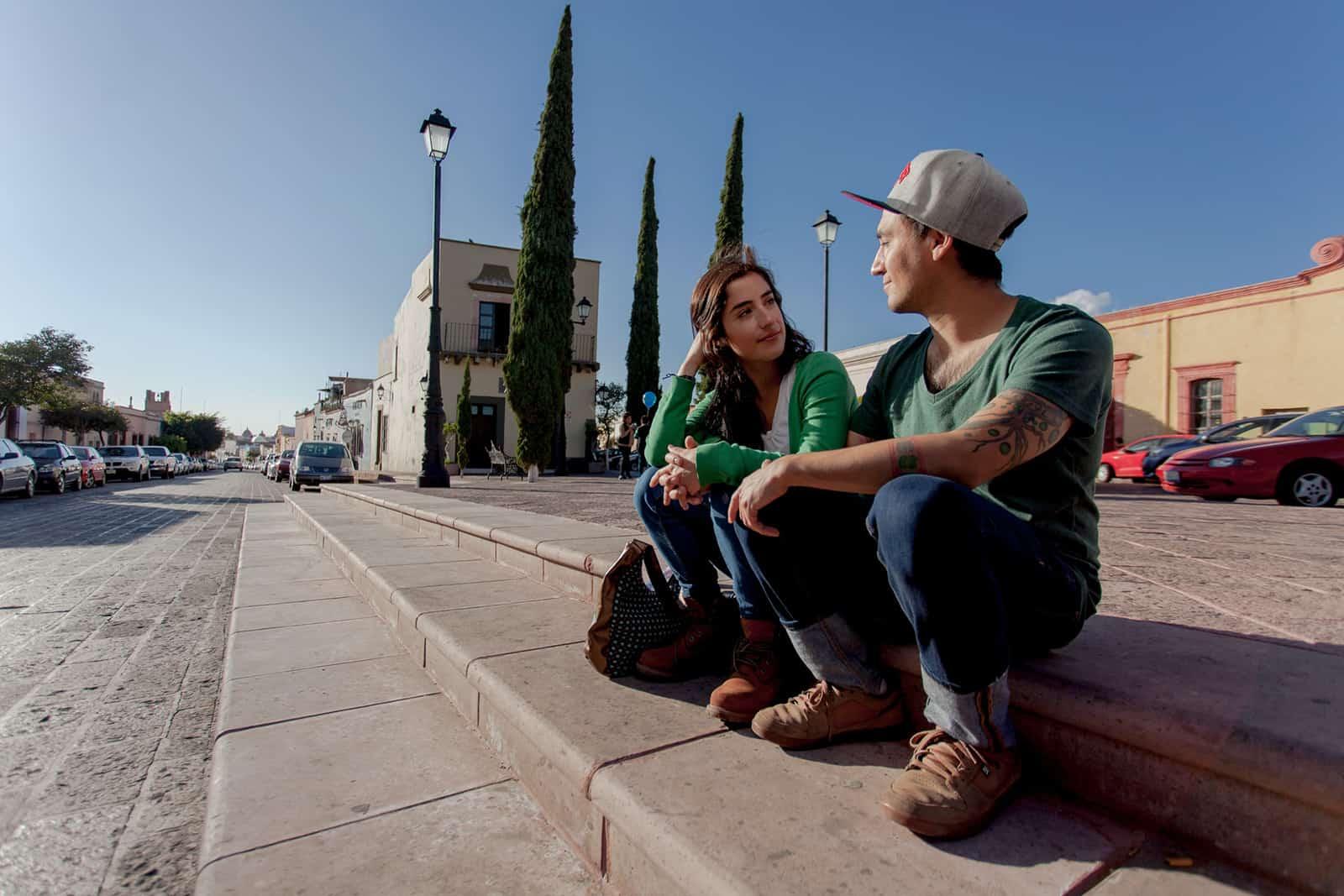 Ein Mann und eine Frau sitzen auf einer Treppe bei einem Date
