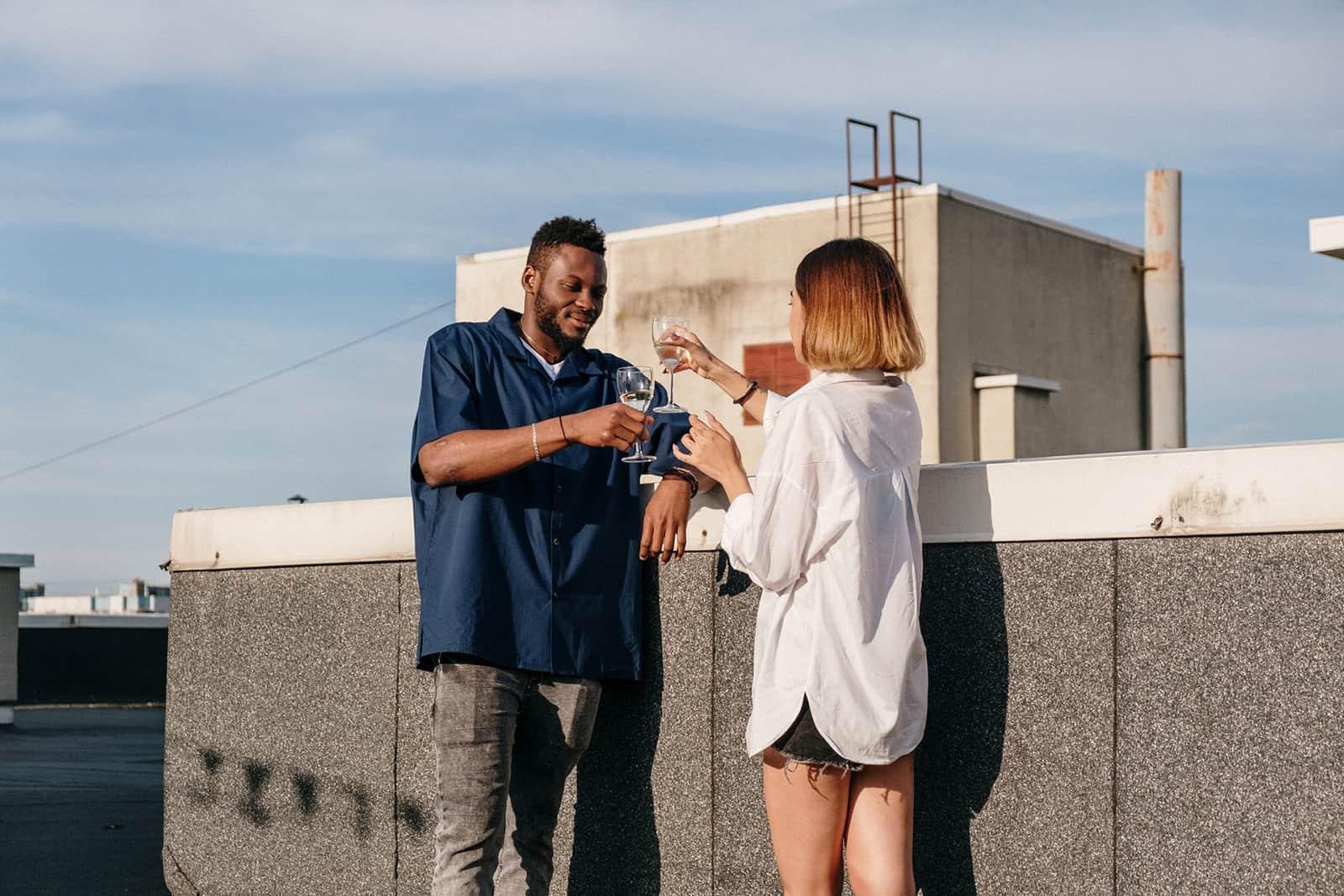 Ein Mann und eine Frau trinken während eines Dates Wein auf einem Dach