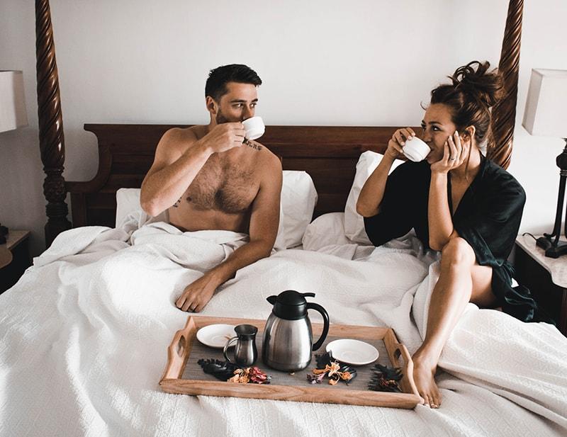 Ein Mann und eine Frau trinken zusammen Kaffee, während sie im Bett sitzen