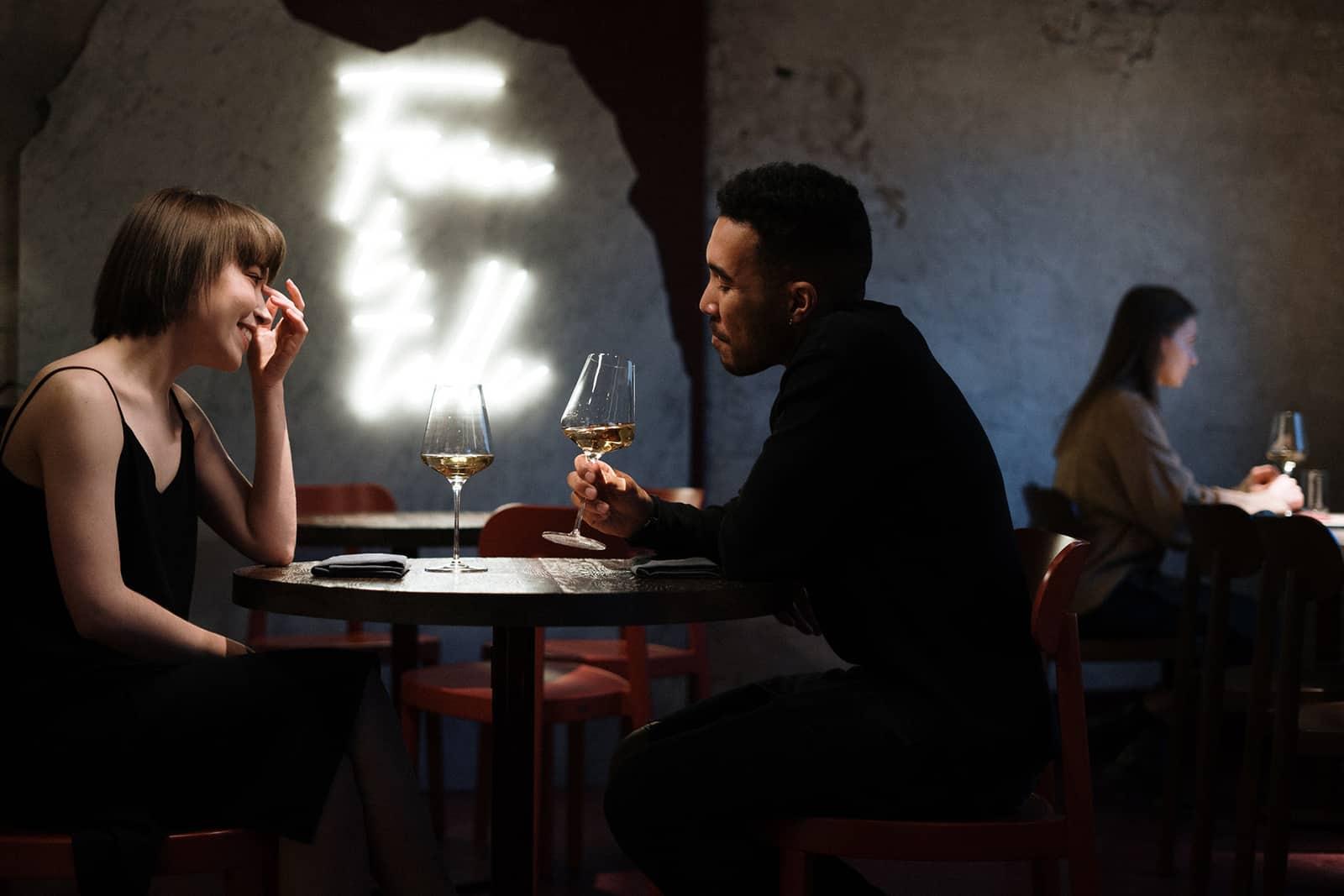 Ein Mann verführt eine Frau, während er im Restaurant ein Glas Wein hält