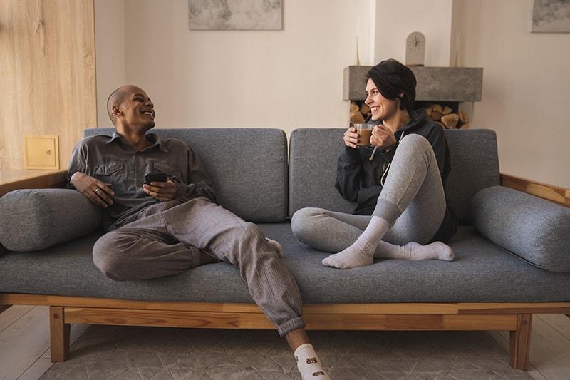 Ein Paar sitzt auf der Couch und redet, während es zusammen Kaffee trinkt