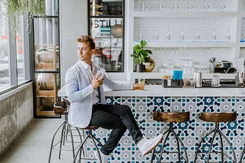 Ein gutaussehender Mann im Anzug sitzt an der Bar