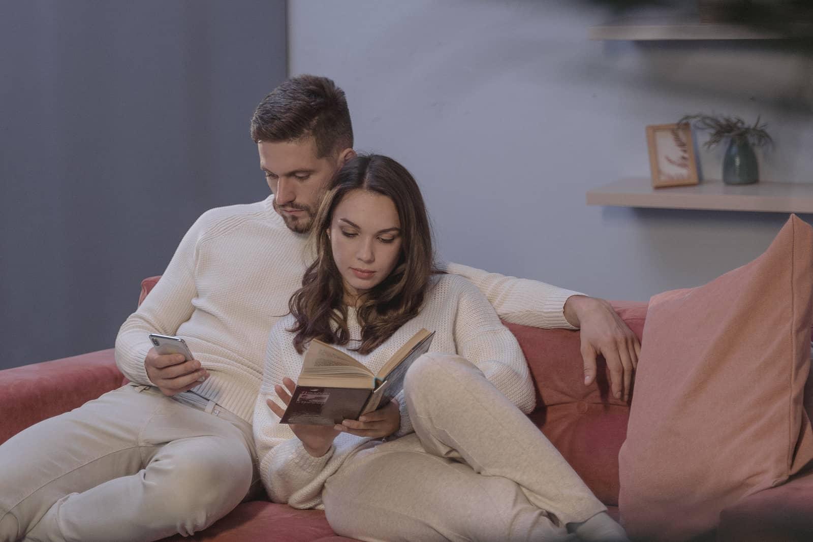 Eine Frau liest ein Buch und ein Mann benutzt sein Smartphone, während sie zusammen auf der Couch sitzen