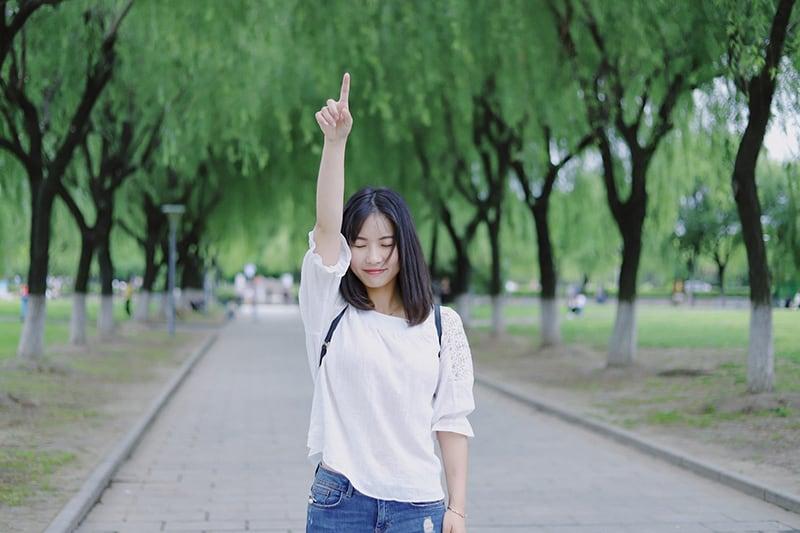 Eine Frau hob ihren rechten Arm mit geschlossenen Augen, während sie auf der Promenade stand