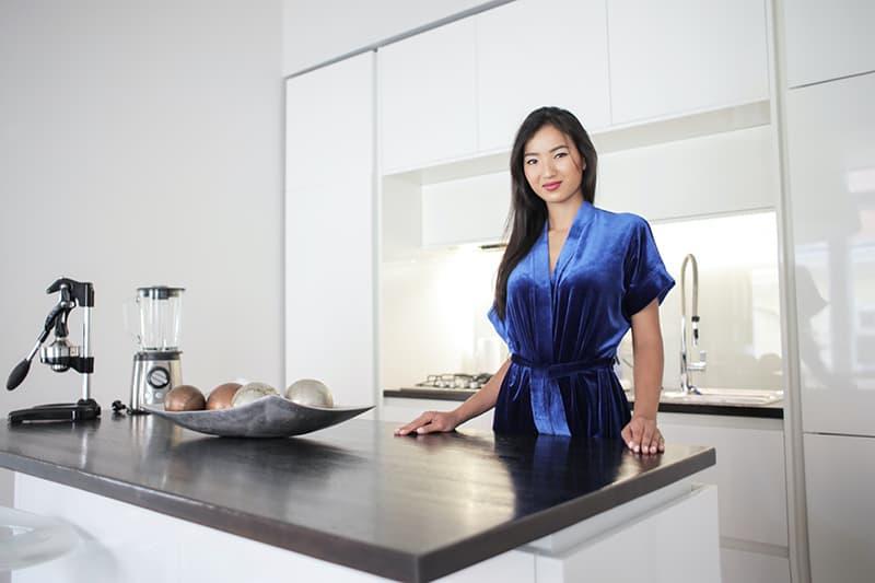 Eine Frau in einem blauen Kleid, die neben der Theke in der Küche steht