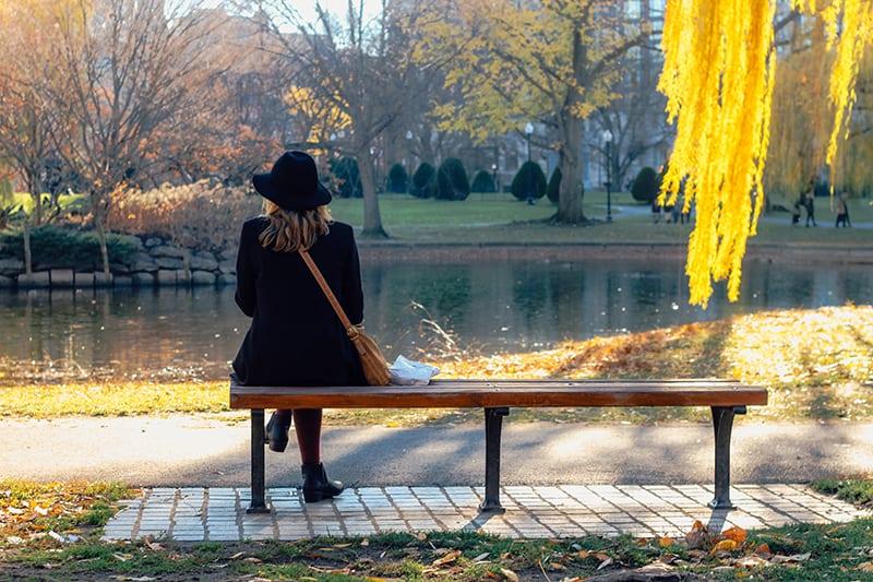 Eine Frau, die auf der Bank in der Nähe des Sees sitzt