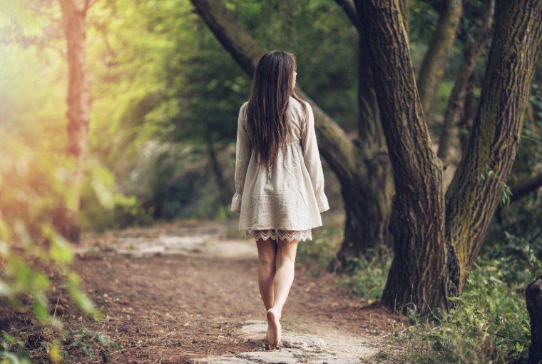 Das Mädchen im Mantel geht die Waldwege entlang