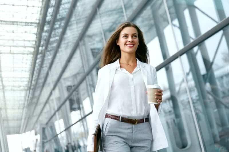 Eine junge Geschäftsfrau geht mit einem Glas in der Hand an der Firma vorbei