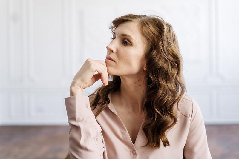 Eine nachdenkliche Frau, die zur Seite schaut und das Kinn mit der Hand berührt