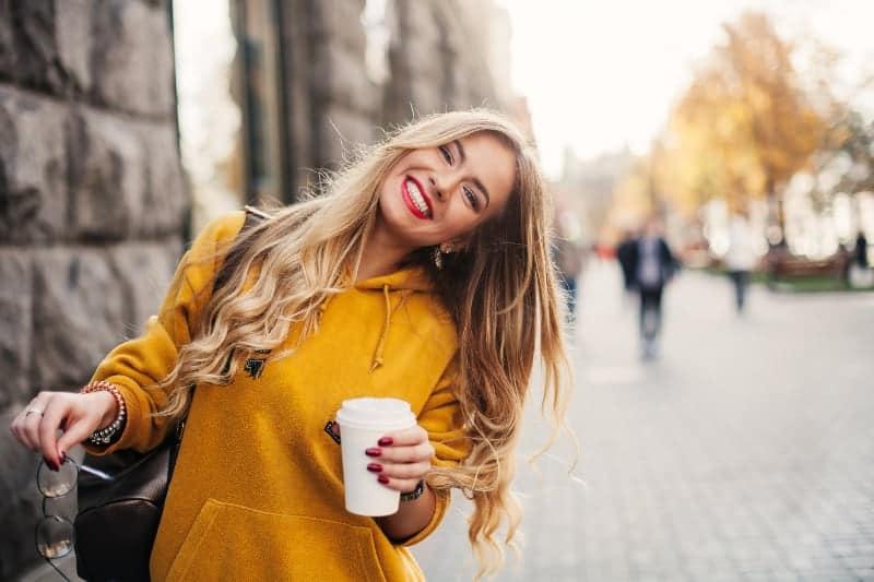 Eine schöne Blondine in einem gelben Sweatshirt lacht und hält einen Kaffee in der Hand