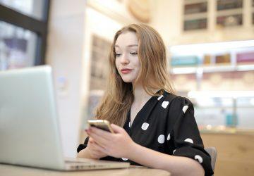 eine lächelnde Frau, die ein Smartphone hält