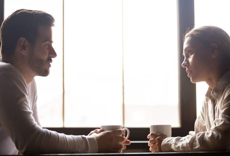 Ernsthafter Mann und Frau sprechen, während sie Kaffee zusammen trinken
