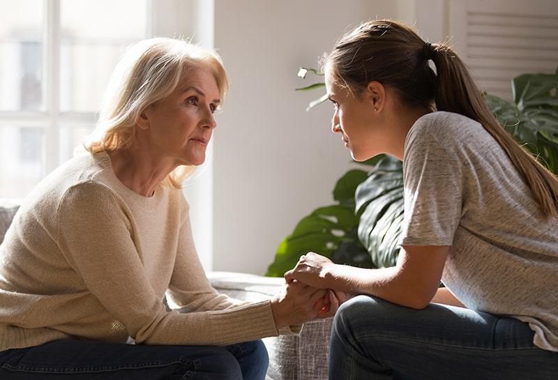 Erwachsene Tochter, die Hände einer Mutter mittleren Alters beim Sitzen im Wohnzimmer hält