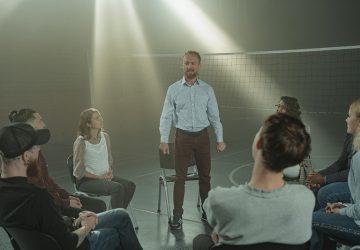 Ein Mann, der vor einer Gruppe von Menschen steht, die auf Stühlen sitzen