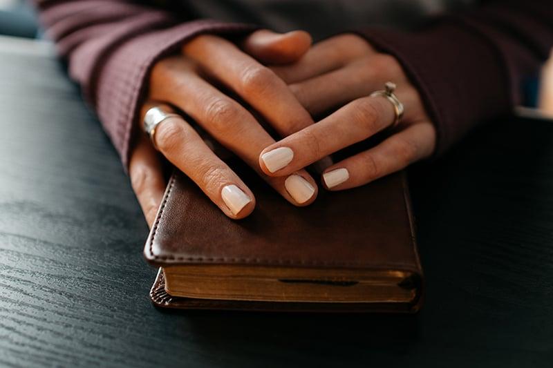 Frau, die Hände auf dem Buch auf dem Tisch hält