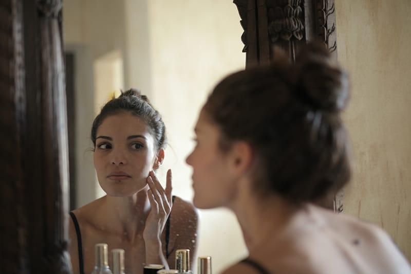 Frau berührt ihre Wange und schaut sich in den Spiegel