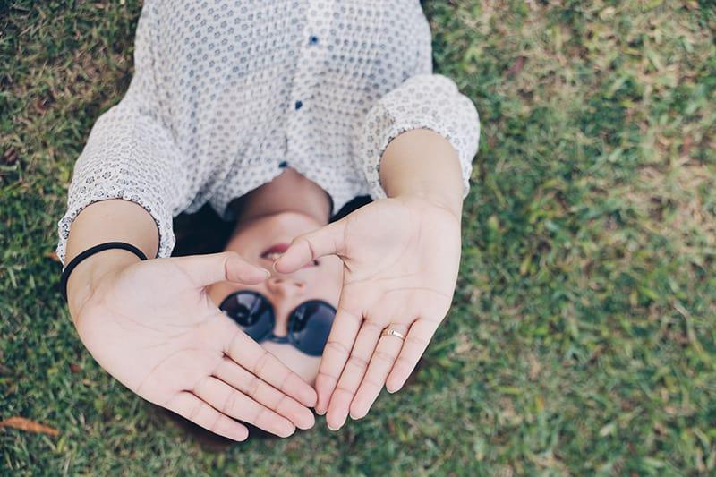 Frau, die mit ihren Händen ein Herz bildet, während sie auf dem Gras liegt